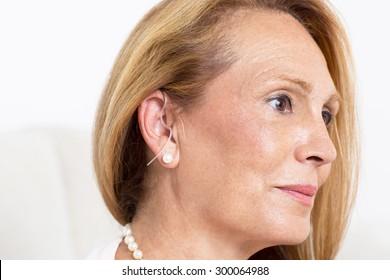 Elderly woman with a deaf-aid