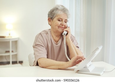 Elderly woman dialing telephone number at home