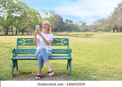 elderly woman is digital addictive social era by using cell phone and looking up something in the sky with right copy space during summer time