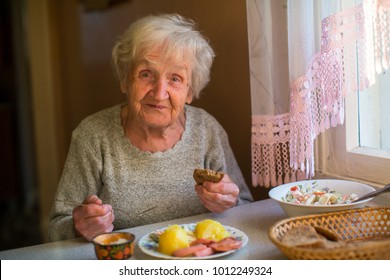 Elderly woman dines at home.