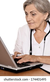 Elderly woman doctor sitting with laptop on white