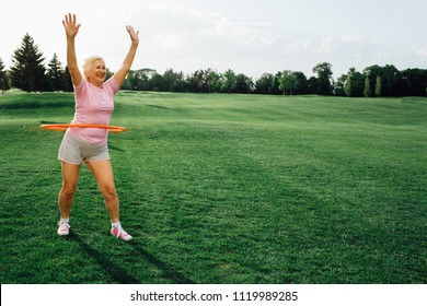 elderly woman does the exercise with hula hoops, laughing and enjoy the rest