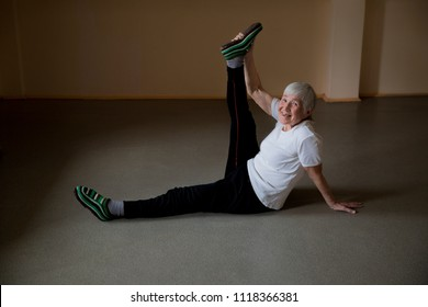 An elderly woman does gymnastics.