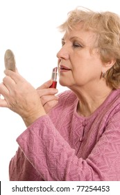 The elderly woman does a make-up isolated