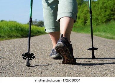 Elderly woman does Nordic Walking on an asphalted field road. Female legs with Nordic Walking poles on a cartway at a sunny day in spring.