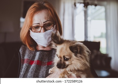 Elderly woman with dog wearing hand made protective face mask, in nursing care home, looking outside window with sadness in her eyes, self isolation due to the global COVID-19 Coronavirus pandemic.