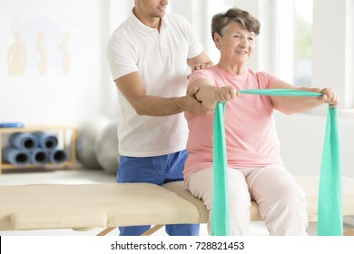 Elderly woman doing active pnf exercises with a teal scarf as a part of her rehabilitation program with a physiotherapist