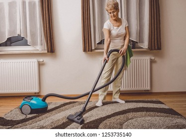 Elderly woman doing woman chores at home. Vacumming the carpet.
