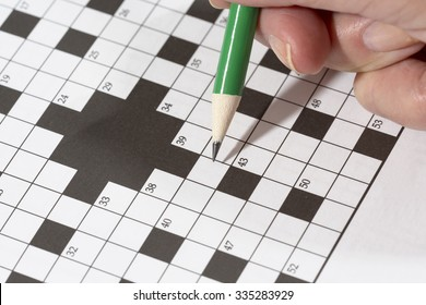 An elderly woman is doing crossword puzzle with a pencil. This is a good exercise for older people to train their brains.