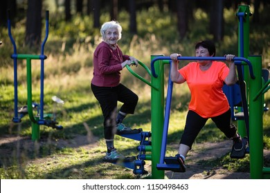 Elderly woman is doing exercises on the sport playground in the Park.