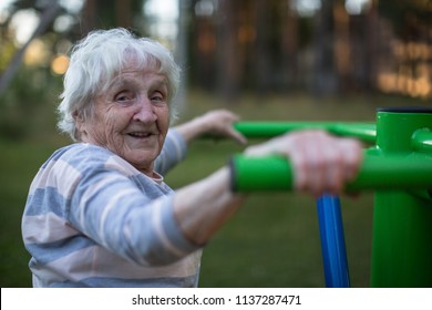 An elderly woman doing morning exercise on the street sport playground.