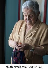 Elderly woman doing needlework at home