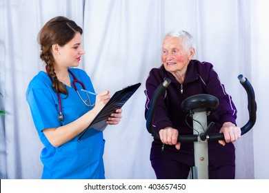 Elderly woman doing sport effort while a kind geriatrician doctor is attending the event in a nursing home.