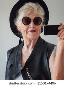 Elderly woman dressed as hipster takes selfie with mobile phone standing in front of mirror.