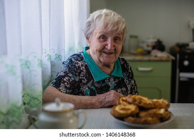 Elderly woman drinking tea with pastries in the kitchen.