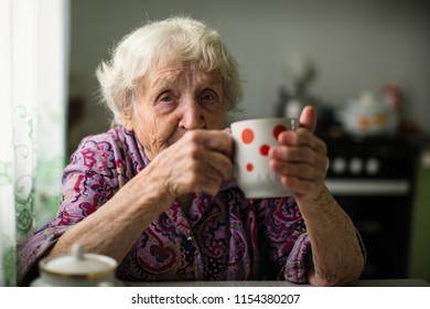 An elderly woman drinking tea sitting in the kitchen.