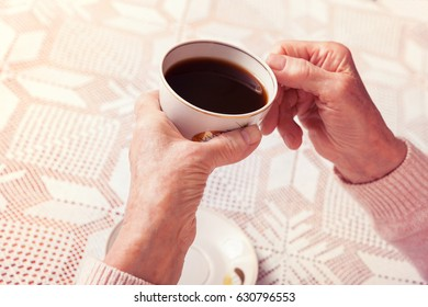 An elderly woman drinks tea at home. Senior woman holding cup of tea in their hands at table close-up. Toned photo