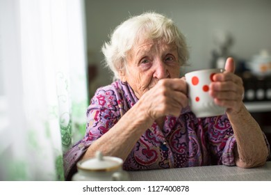 An elderly woman drinks tea sitting in the kitchen.