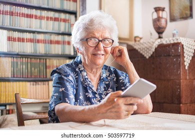 Elderly woman with earphones listening to music on smartphone at home.