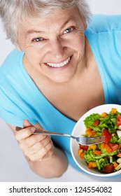 Elderly woman eating salad