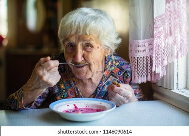 An elderly woman eating soup borsch sitting at the table.