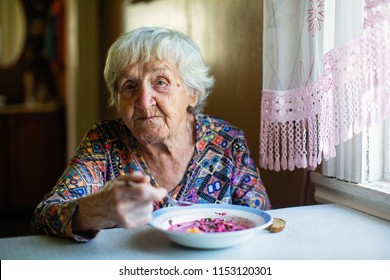 An elderly woman eating soup sitting at a table in the house.