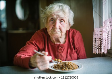 Elderly woman eats buckwheat porridge sitting at the table.
