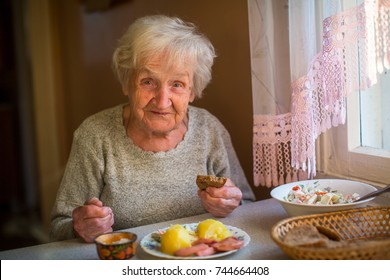 An elderly woman eats at home.