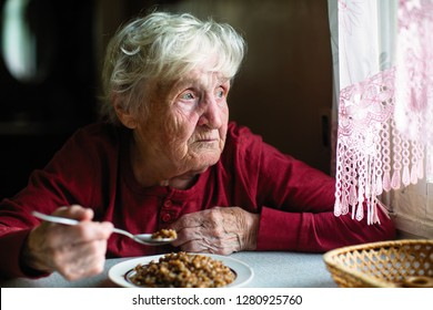Elderly woman eats sitting at the table.