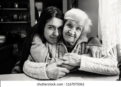 Elderly woman in an embrace with an adult granddaughter in a village house. Black and white photo.