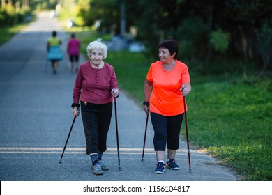 An elderly woman is engaged in Nordic walking with her adult daughter.