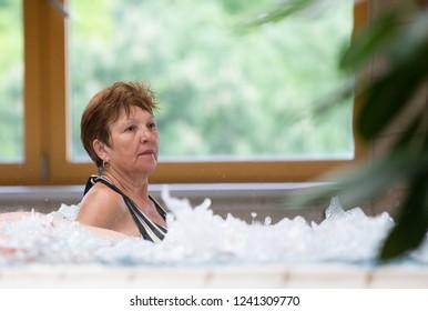 Elderly woman enjoying in pool with hot water in spa resort