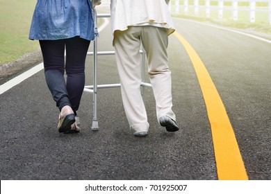 Elderly woman exercise walking in road with daughter