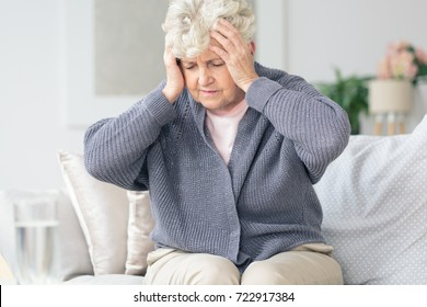 Elderly woman feeling sick holding head having painful migraine headache