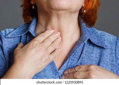 An elderly woman feels her thyroid gland.