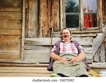 Elderly woman in front of her old house