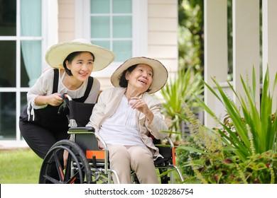 Elderly woman gardening in backyard with daughter