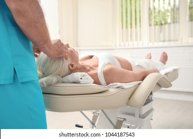 Elderly woman getting head massage at physical therapy office