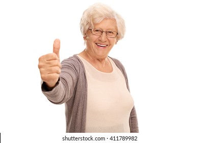 Elderly woman giving a thumb up and looking at the camera isolated on white background