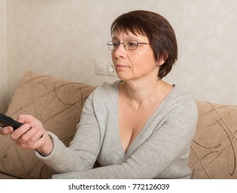 Elderly woman in glasses sitting on couch with remote control TV in hand