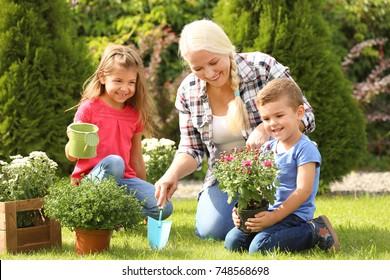 Elderly woman with grandchildren working in garden