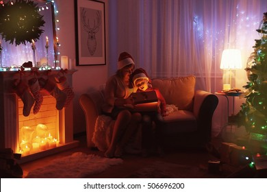 Elderly woman with grandson opening Christmas present while sitting on sofa in living room