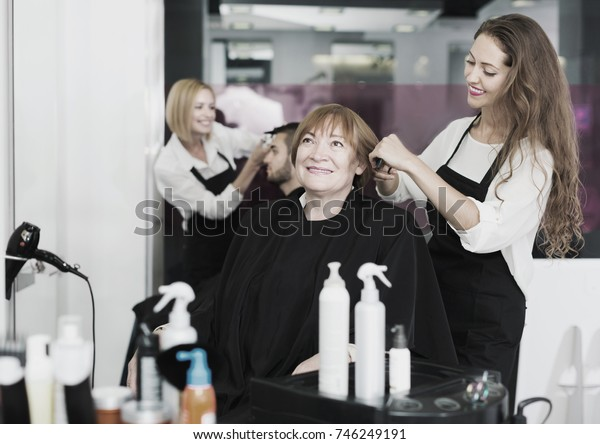 Elderly woman at the hair salon with girl barber doing haircut  and smiling