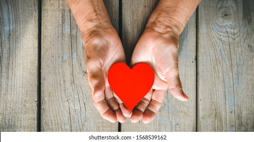 Elderly woman hands closeup holding red heart. Rustic wooden table background. Love, warmth, take care concept, Valentines, mothers day, donate, help.