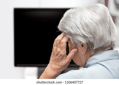 Elderly woman with headache sitting in front of a desk or tv, concept mental overload and stress, copyspace
