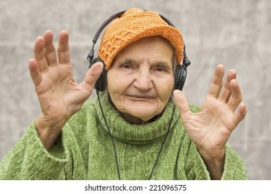 Elderly woman with headphones listening to music.