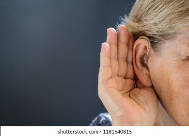 Elderly woman with hearing aid on grey background. Close up. Defect and hearing loss concept.