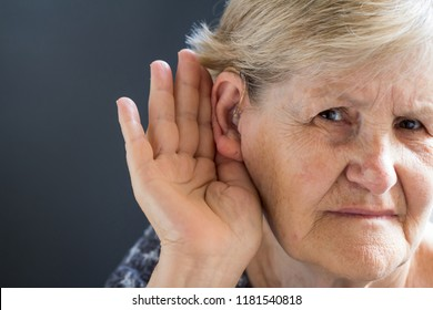 Elderly woman with hearing aid on grey background. Age-related hearing loss, symptoms and treatment concept.