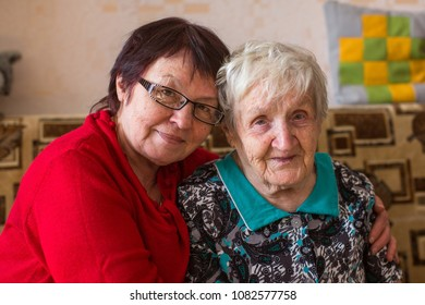 Elderly woman with her adult daughter on the couch.