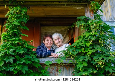 Elderly woman and her adult daughter looking out the window of the village house.